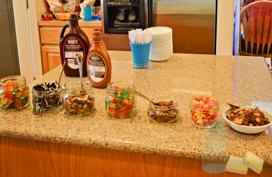 Small mason jars with ice cream toppings for ice cream bar