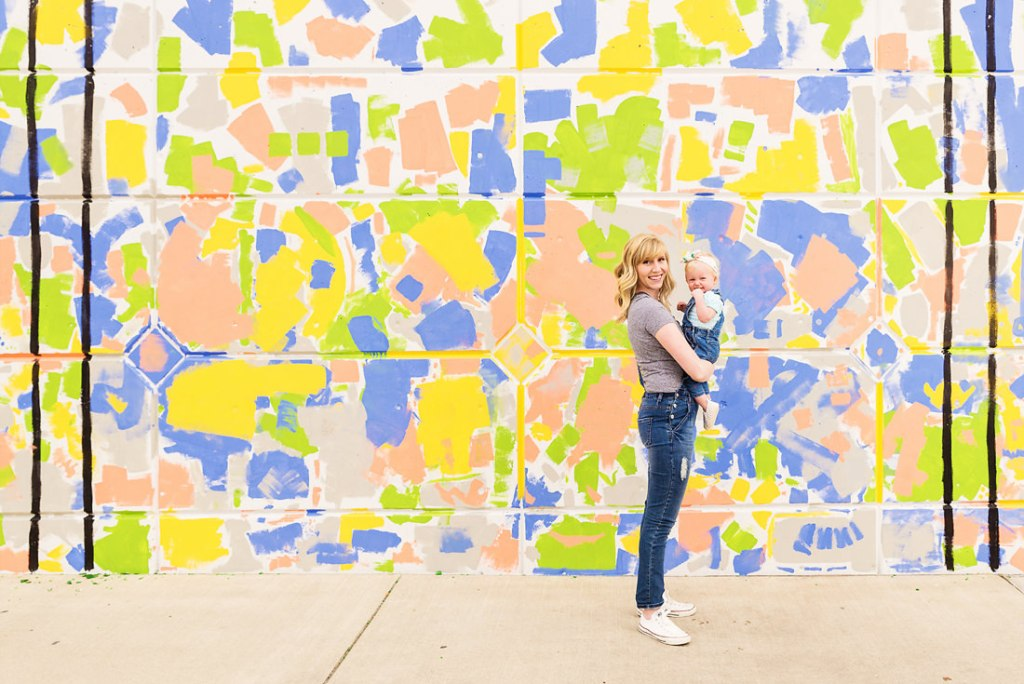 Little girl with headband and painted overalls mommy and me photo standing in front of colorful Provo Utah mural