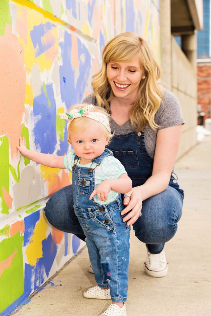 Little girl with headband and painted overalls mommy and me photo standing next to colorful wall