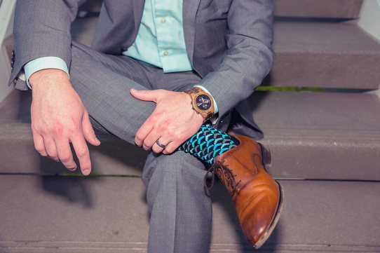 man wearing jord conway series walnut jet black unique wood watch joseph aboud gray suit steve madden shoes colorful socks legs crossed