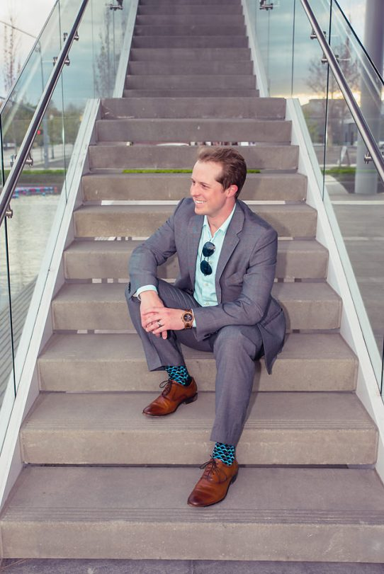 man wearing jord conway series walnut jet black unique wood watch joseph aboud gray suit steve madden shoes colorful socks sitting on outdoor staircase