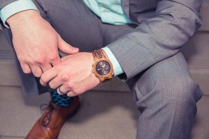 man wearing jord conway series walnut jet black unique wood watch joseph aboud gray suit steve madden shoes colorful socks sitting on stairs